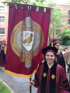 Megan Monahan, PhD with the banner of the Graduate School of Arts and Sciences